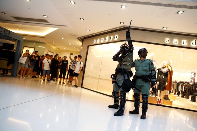 香港警察一度舉槍,向商場內圍觀市民示警。(路透)