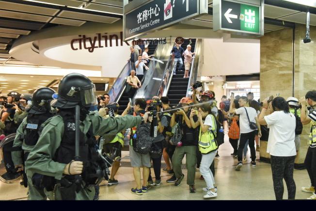 有防暴警察在太古城中心內舉起胡椒噴劑指向市民。(歐新社)