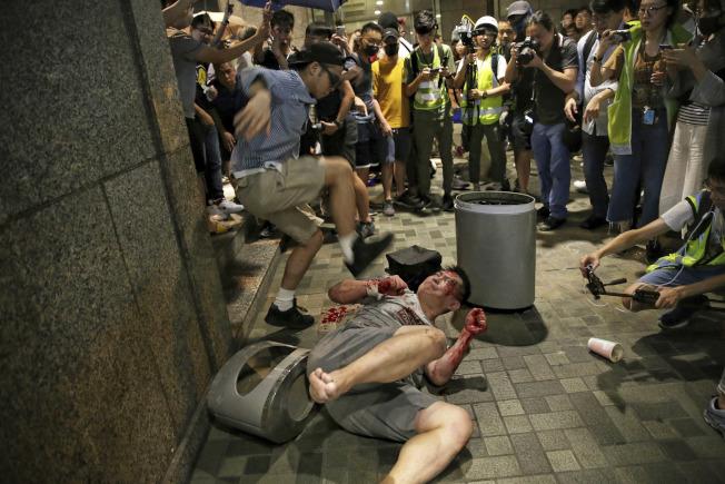 香港民眾3日舉行的「反警暴七區行街(逛街)」行動,於晚上7時左右爆發流血襲擊事件,一灰衣男子持刀刺傷五人,並咬掉區議員趙家賢左耳。圖為兇嫌被民眾制伏倒地。(美聯社)