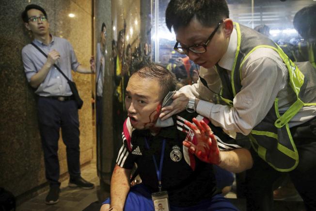 香港民眾3日舉行的「反警暴七區行街(逛街)」行動,於晚上7時左右爆發流血襲擊事件,區議員趙家賢在制止灰衣男子持刀傷人時,反遭咬斷左耳。圖為趙家賢接受急救。(美聯社)