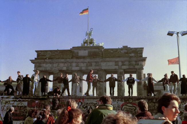 柏林圍牆倒塌在本周屆滿30周年,圖為1989年11月10日東柏林民眾在圍牆上頭跳舞,慶祝兩德邊境開放的檔案照片,背後就是著名的布蘭登堡門。(美聯社)