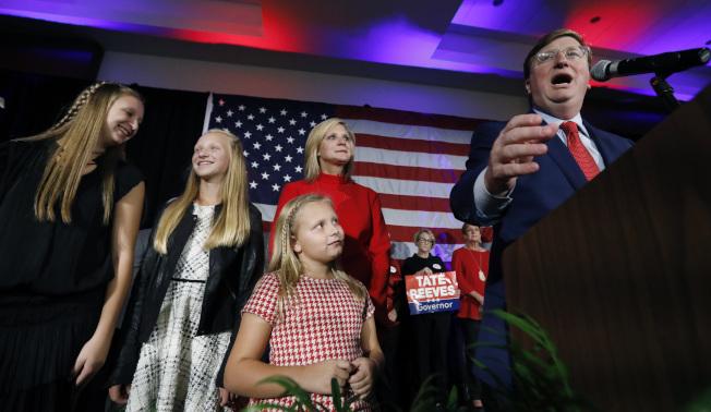共和黨籍的瑞維斯(右)當選密西西比州州長後,全家上台接受支持者歡呼。(美聯社)