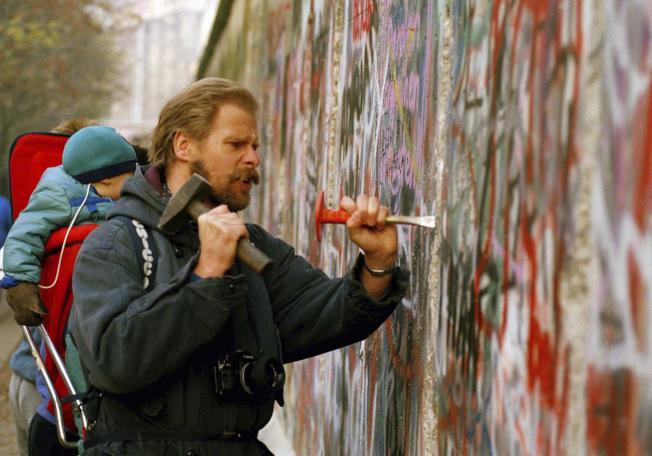 前蘇聯及東德放棄柏林圍牆的鐵幕政策後,全世界的年輕人都湧到西柏林,參與拆除圍牆工作。圖為1989年11月的拆牆資料照片。(美聯社)