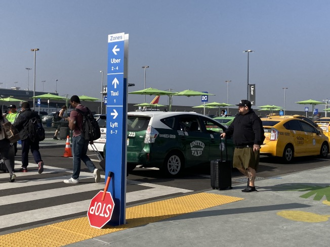 洛杉磯國際機場新設叫車接機區,旅客若要上優步、Lyft、或計程車,需搭乘接駁車或步行至一號航廈站旁邊的停車場。(記者謝雨珊/攝影)