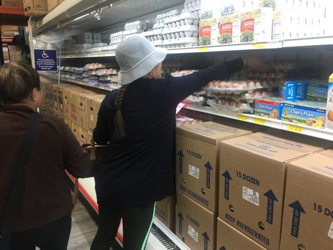 民眾正在選購特價雞蛋。(記者王全秀子/攝影)
