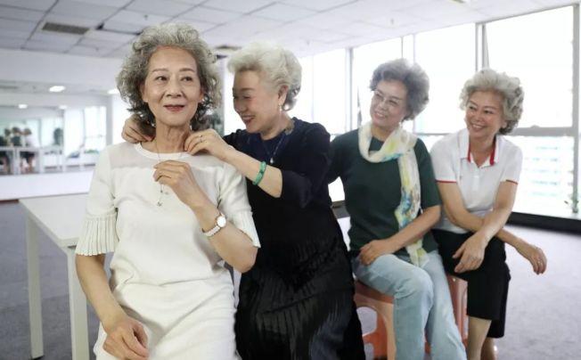 張淑貞(左二)在拍攝前為樊其揚(左一)戴上項鏈 。(取材自新京報)