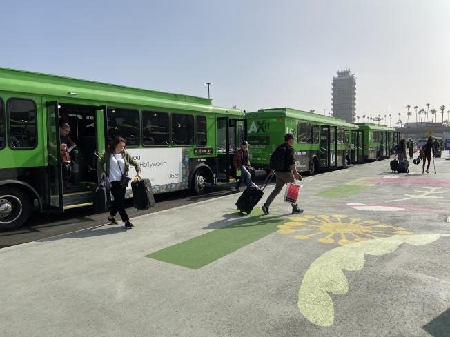 機場在尖峰時段,有43台綠色LAX-it接駁車接送乘客到叫車專屬區。(記者謝雨珊/攝影)