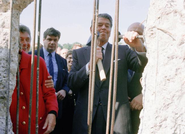 美國前總統雷根當年參與推倒柏林圍牆,這是他在1990年象徵性的動手拆除圍牆。(美聯社)