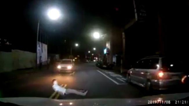 一名男子在新北市汐止區衝進車道,倒在兩輛行駛中汽車前方,隨即起身捶打地面後離開,被行車記錄器拍下上傳網路,警方檢視畫面懷疑是製造假車禍。圖/翻攝自臉書「汐止集團」