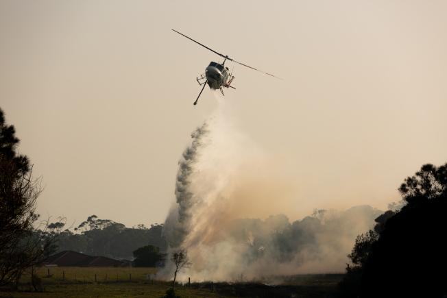 灌木林大火肆虐新南威爾斯省,一架直升機7日在該州上空灑水滅火。(歐新社)