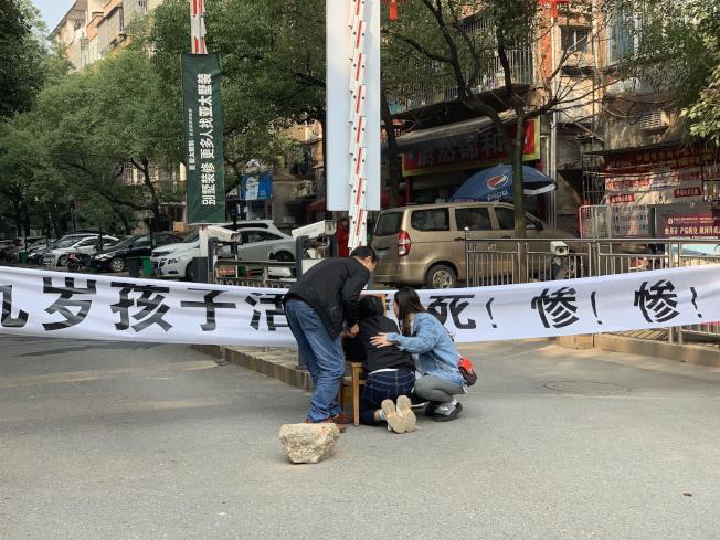 羅姓男童的媽媽8日上午趴在小區門口兒子的遺像前。(取材自新京報)