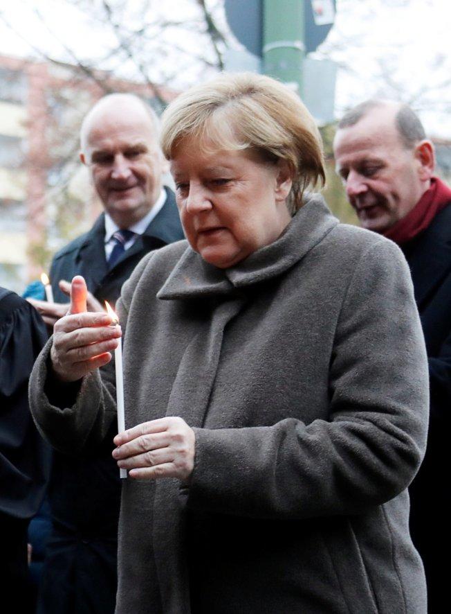 德國總理梅克爾9日點蠟燭紀念試圖翻越柏林圍牆被殺的民眾。(路透)