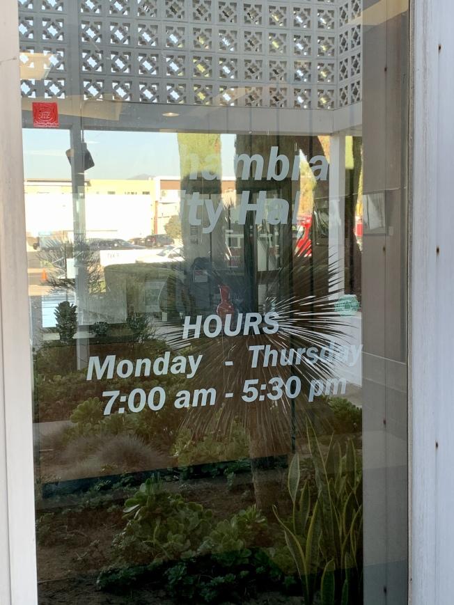 阿罕布拉市政府門上已經貼出新的工作時間。(記者陳開/攝影)