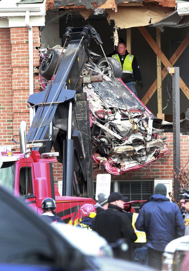新澤西州10日發生一起車禍,一輛保時捷跑車失控撞入一棟建築物的二樓,車上兩人當場死亡。圖為吊車把撞成一堆廢鐵的保時捷跑車吊離現場。(美聯社)