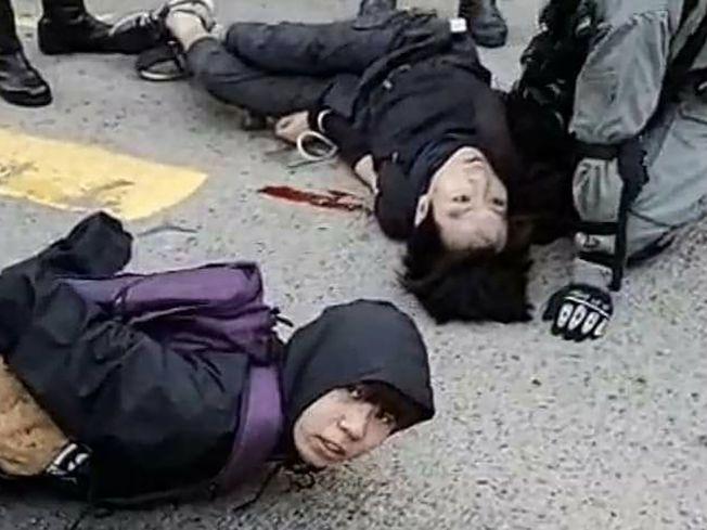 香港部分市民11日發起「大三罷」,警方全面搜捕示威民眾,近距離實彈射擊三槍,兩人流血倒地。(Getty Images)