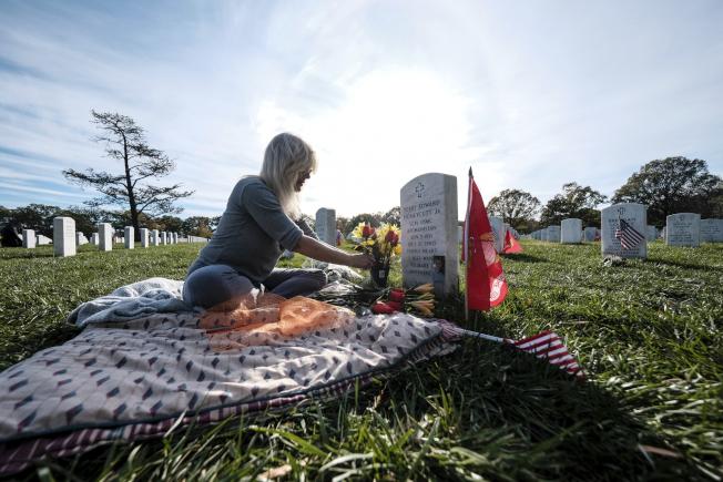 在維吉尼亞州阿靈頓,一位母親坐在她兒子的墓碑前。(美聯社)