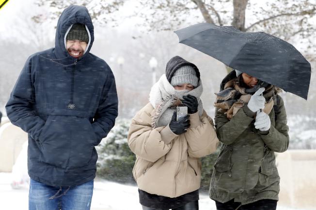 芝加哥全副武裝的民眾冒著風雪在外行走。(美聯社)