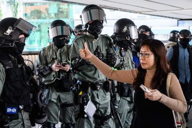 香港示威抗議幾無寧日,警民衝突也導致各自的支持者,像同溫層般明顯集結;彼此立場堅持且鮮明,幾無互信與對話理解的空間與可能。圖為一名女士11日向警察伸出大拇指,肯定警察的行動。(Getty Images)