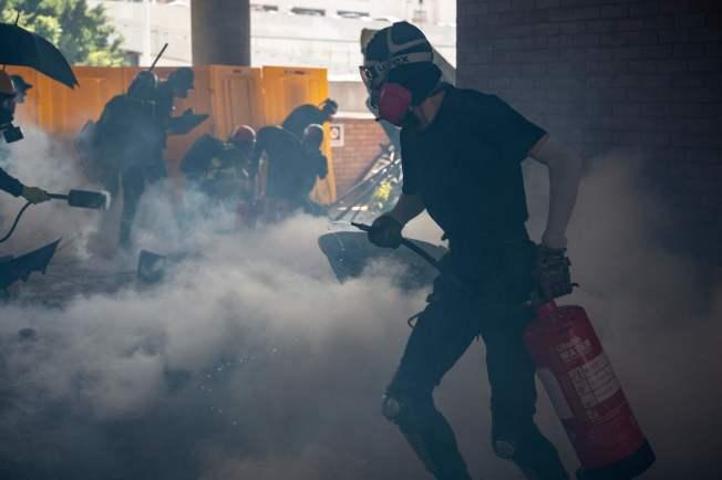 香港警察11日首次進入大學校園,向戴著頭盔和蒙面的示威者發射催淚彈。圖為示威者在躲避警方的催淚彈。(Getty Images)