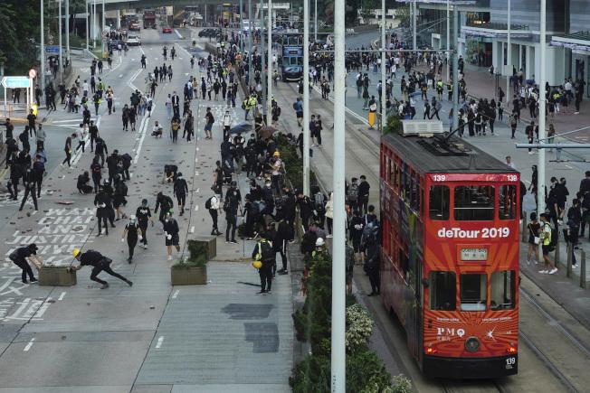 香港因「反送中」導致的警民衝突11日加劇升溫,這個亞洲金融中心在數月的無解抗爭中,原本自豪的社會與經濟活動幾近癱瘓。圖為抗爭後,一輛掛著「2019年繞道」標示的紅色雙層巴士,在抗爭後行過不少黑衣人聚集、滿目瘡痍的街道。(美聯社)