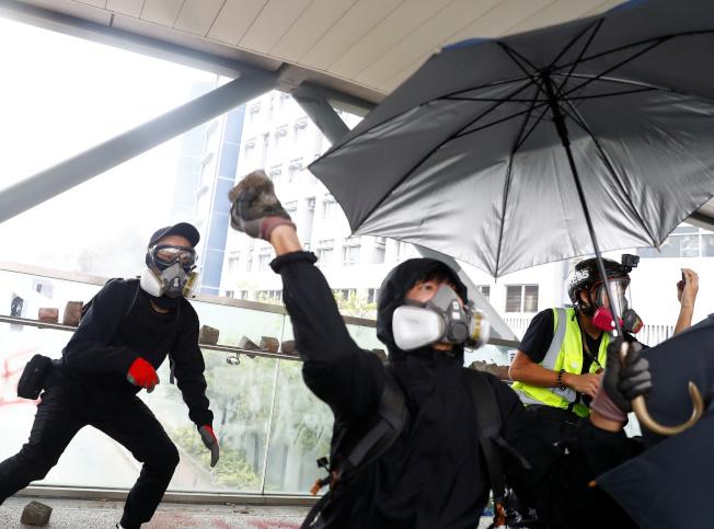 示威者行人天橋向地面扔擲磚塊攻擊警察。(路透)