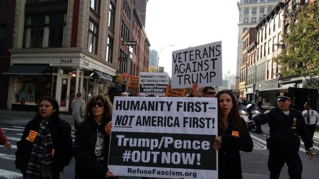 反川普組織手舉標語抗議「人民優先而非美國優先」。(RefuseFascism提供)