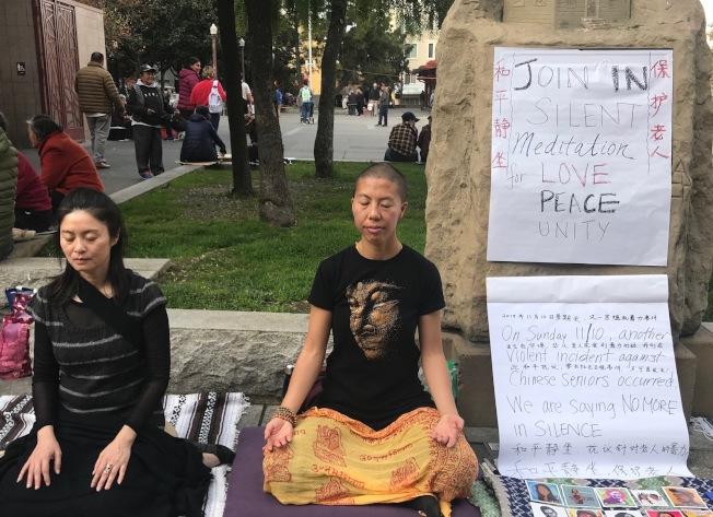 余嘉雯(右)在花園角以禪修和平靜坐的方式,抗議周末發生的三名華裔老人遭暴力攻擊的事件,招霞(左)加入靜坐行動。(記者李秀蘭/攝影)