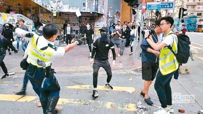 一名香港警察(左)11日在西灣河用槍瞄準一名示威者,隨後開槍擊中。 路透