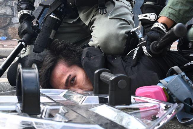 警方在校園發射催淚彈之後,有一名男子被扣下。(美聯社)