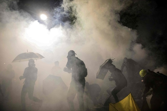 示威者在警方發射的催淚彈濃煙之下。(Getty Images)