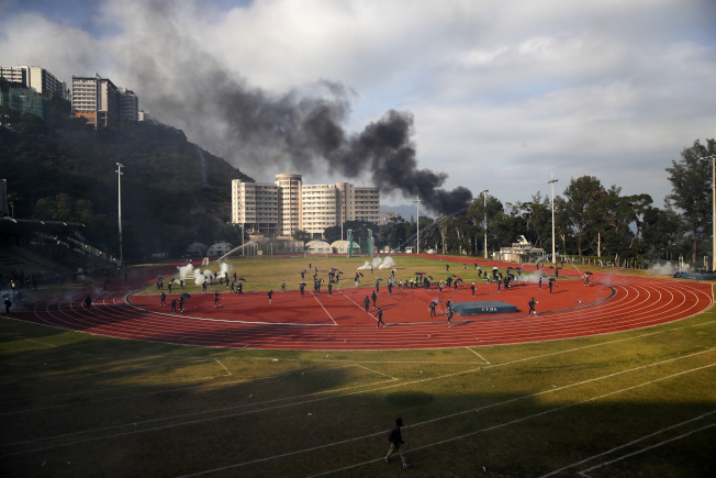 港中大校園跑道上,學生試圖清理警方發射的催淚彈。(美聯社)