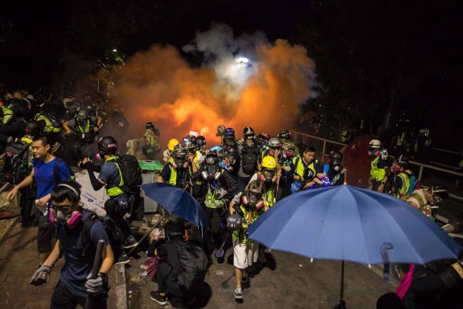 記者和示威者試圖躲避警方發射的催淚彈。(Getty Images)