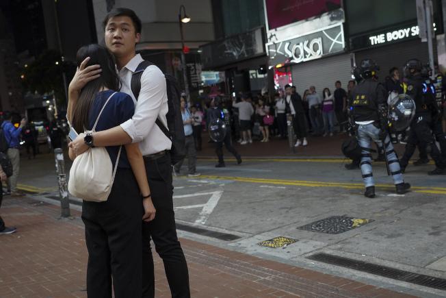 港警12日在淺水灣驅離民眾,一對香港情侶在街頭相擁。(美聯社)