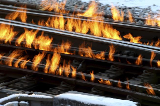 芝加哥部分火車鐵軌12日結冰, 工人在軌道放火以使火車順利通行。(美聯社)