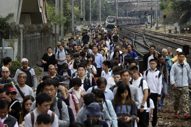 由於鐵路遭示威者破壞,香港通勤市民只得下車步行。(美聯社)