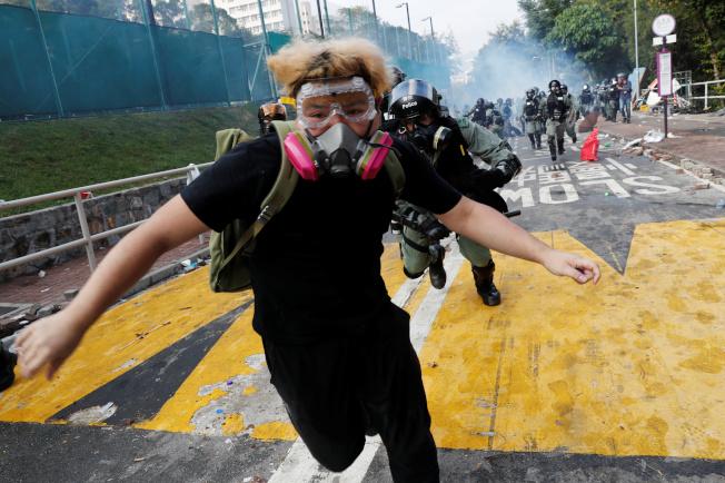 戴著口罩與護目鏡的學生在香港中文大學內逃避警方追捕。(路透)