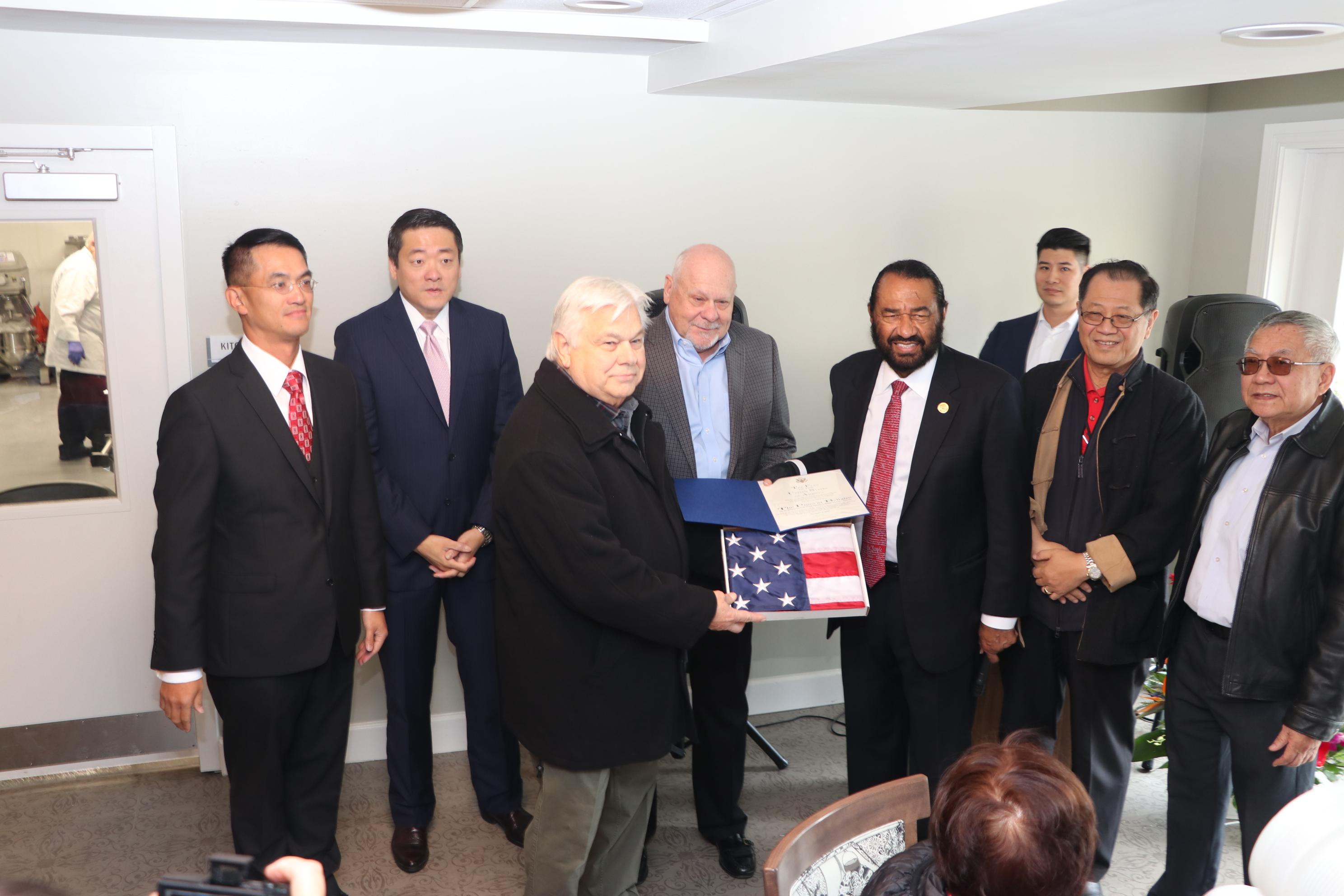 國會議員Al Green(前排右三)帶來一面曾在國會山莊飄揚的國旗贈予「松園居」,表彰他們為社區的貢獻。