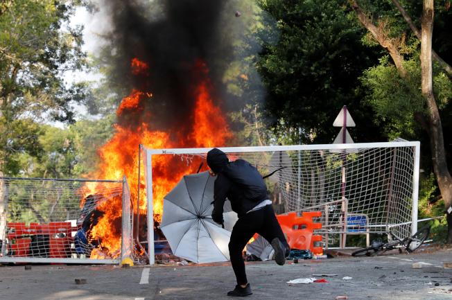 學生在香港中文大學校園內,對警方投擲石塊。(路透)