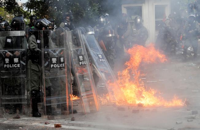 學生在香港中文大學校園內與警方對峙,並對警察投擲自製汽油彈。(路透)