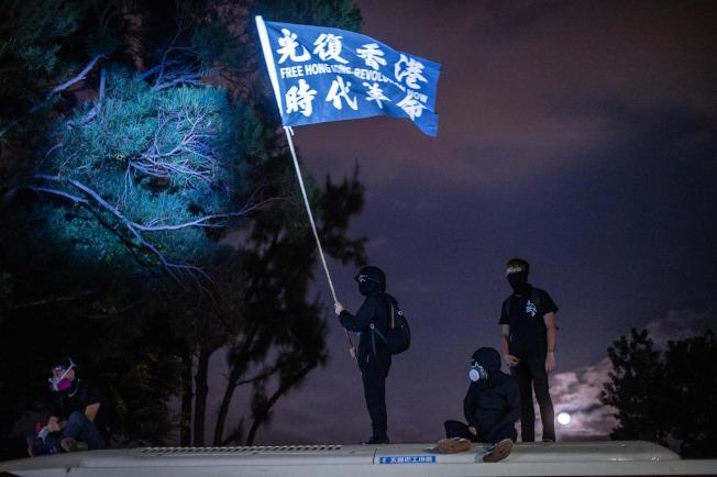 學生在香港中文大學與警方對峙期間,揮舞「光復香港,時代革命」旗幟。(Getty Images)