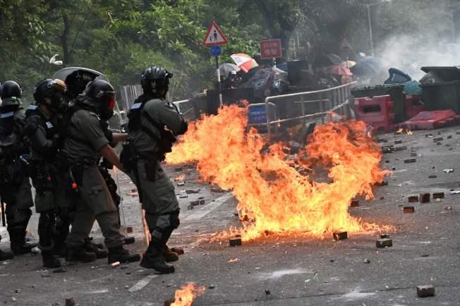 學生在香港中文大學校園內與警方對峙,警方發射催淚彈(左),學生向警察投擲自製汽油彈。(Getty Images)