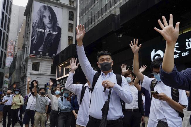 香港中環白領在街上比出「五」的手勢,支持示威者的「五大要求」。(美聯社)