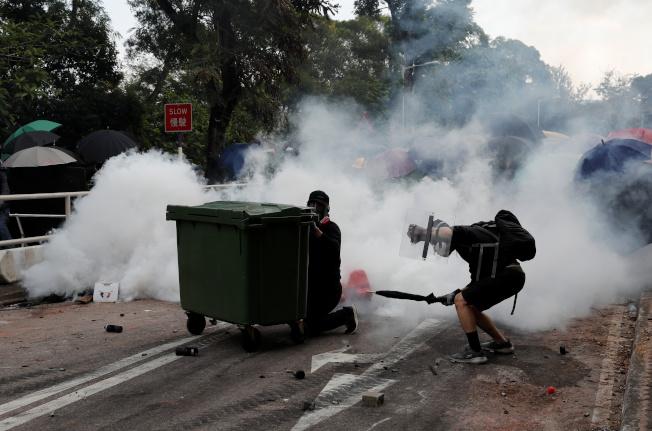 學生在香港中文大學校園尋找掩蔽物,與香港警方對峙。(路透)