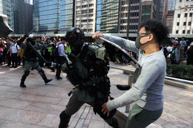 香港警民衝突,暴力升級。反送中示威者13日再度於中環發起「快閃」示威行動,圖為防暴警察與一名示威者扭打 。(路透)