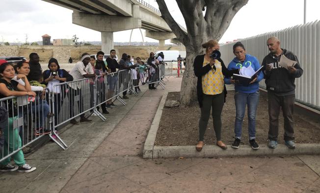 圖為有意申請庇護者在美墨邊境排隊等候。(美聯社)