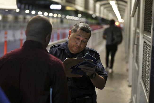 川普政府13日對非法入境的尋求庇護者提出新規定,拒絕多數人申請工作許可。圖為美墨邊境的移民官員檢查有意申請庇護者的證件。(美聯社)