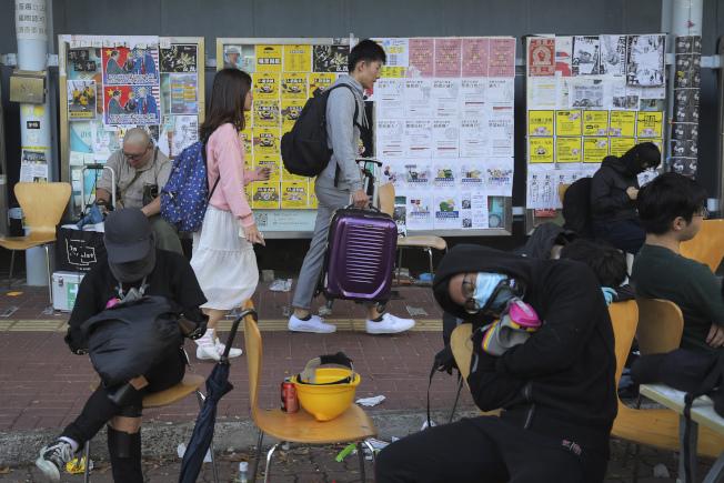香港警民衝突加劇,並蔓延至大學校園。圖為重災區香港中文大學大陸學生13日撤回大陸時,經過黑衣示威者。(美聯社)