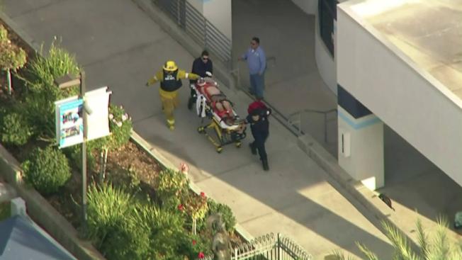 槍案發生後,一名受傷學生在醫護人員護送下往醫院接受治療。(美聯社)