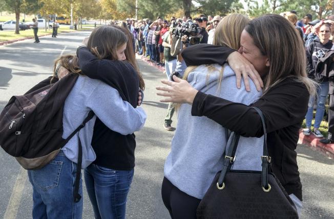學生與家長團圓時,抱著哭成一團。(美聯社)