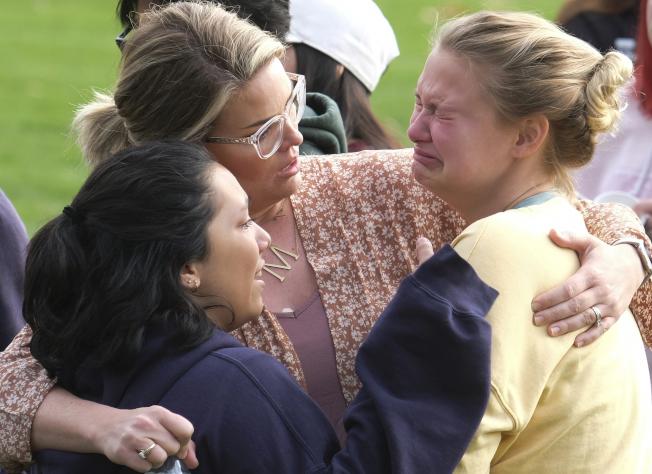 在等待與家人團聚過程中,學生互相擁抱、彼此安慰。(美聯社)